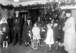 7th January 1927. The Lord Mayor, Alderman Hugh Lupton, and the Lady Mayoress, Ella Lupton, wearing their chains of office, attend a Christmas Party organised for the young residents of Meanwood Park Hospital or 'Colony' as it was then known. Here, a huge christmas tree has been festooned with fairy lights and ornaments, and a frieze of evergreen branches decorates the walls. The Lady Mayoress is taking an interest in a little girl and her dolls pram and there are various other toys beneath the Christmas Tree. The Matron of Meanwood Park Colony in 1927 was Miss Georgina Langdown.