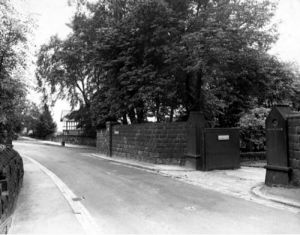 "26/07/1950. Picture shows Spen Lane looking south east towards Abbey Walk and Morris Lane junction. The entrance to the property called ""Crooked Acres"" is visible to the right. Trees are visible throughout the whole picture. The old house can be seen poking through the trees in the far right hand side of the road."